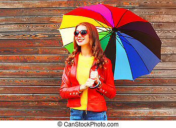 Portrait smiling woman with colorful umbrella in autumn over wooden background