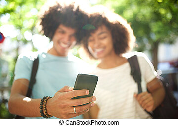 smiling young african american couple standing outside looking at cellphone