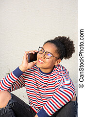 smiling young african american girl sitting and talking with cellphone