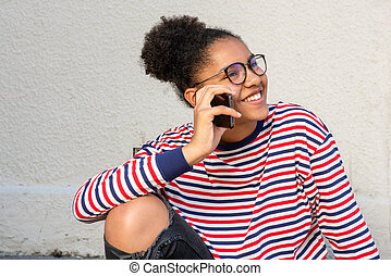 smiling young african american girl sitting and talking with mobile phone