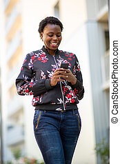 smiling young african woman walking in city looking at mobile phone