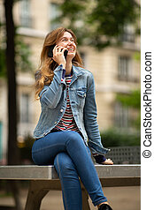 smiling young woman sitting outside in park talking with cellphone
