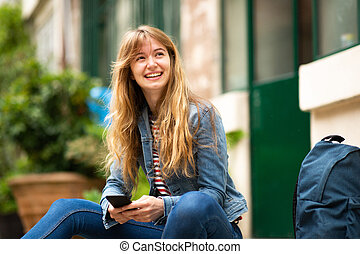 smiling young woman sitting outside with mobile phone