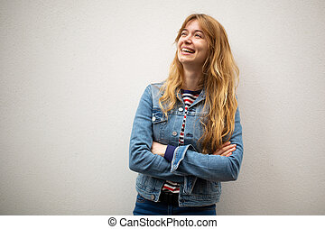 smiling young woman with arms crossed and looking away against white background