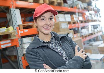 portrait, sourire, bras, entrepôt, traversé, ouvrier, femme