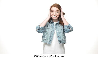 Portrait surprised ginger woman in denim shirt looking at the camera over white background