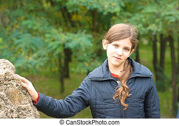 Portrait teen girl and big stone