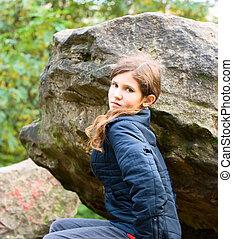 Portrait teen girl on big stone