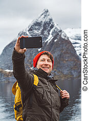 Portrait traveler man taking self-portrait a photo with a smartphone. Tourist in a yellow backpack standing on a background of a mountain. Traveler walks, takes photo in the mountains.
