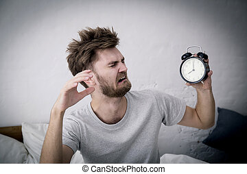 Portrait upset angry young man screaming at alarm clock on bedroom. Employee running late. Time management with business concept