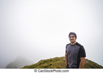 portrait with a tourist on the mountain with a fog
