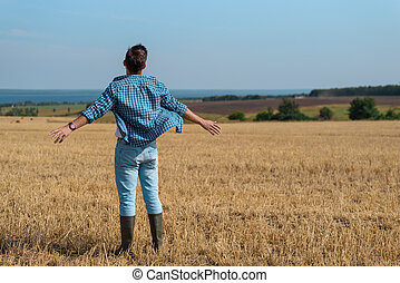 Portrait with back of a man in jeans, shirt, rubber boots in the field with his hands open, the concept of freedom, motivation, movement, copy space