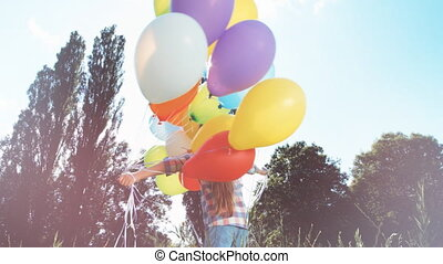 Portrait with Lens flare. Girl spinning with balloons and looking at camera against the sun
