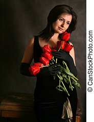 Portrait of the beautiful girl with red tulips