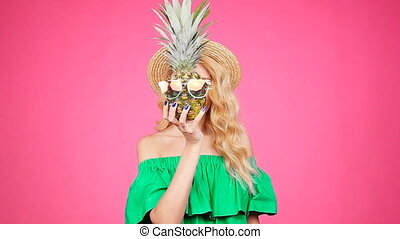 Portrait woman and pineapple with sunglasses over pink background