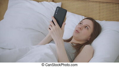 Portrait woman in casual clothing making facetime video ...
