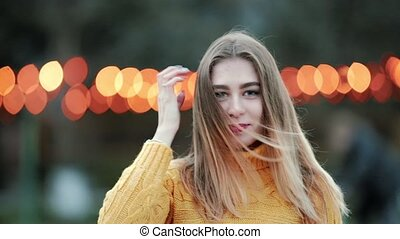 Portrait Woman looks at the camera in front background of orange lights wind blows in evening city