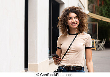 young african american woman smiling on city street with mobile phone and earphones