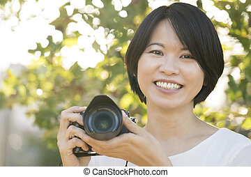 Portrait young Asian woman with camera