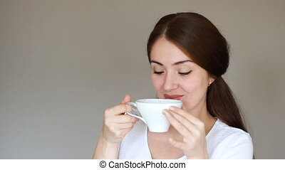 Portrait Young beautiful woman drinks a hot drink from a...
