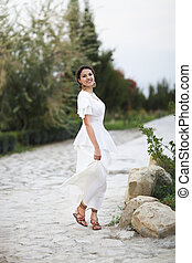 Portrait young bride with brunette hair in white wedding dress and vintage gold jewelry earrings