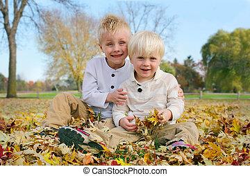 Portrait Young Children Outside in Fallen Autumn Leaves