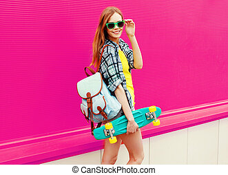 Portrait young cool smiling woman with skateboard on pink background