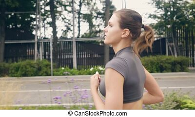 Portrait young fitness woman running at morning jog on...