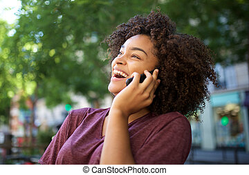 young laughing african american woman talking with cellphone outdoors