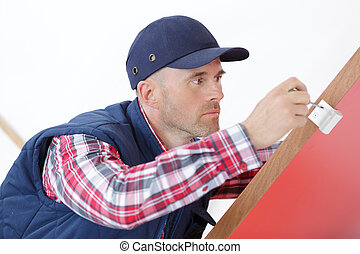 portrait young male carpenter repairing door lock