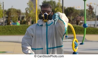 Portrait of a young man in a protective suit, gloves, goggles and a respirator looks into the camera and shows a thumb up, then thumb down, OK and removes the respirator and goggles. Corona virus health protection concept. Slow motion. Close up.