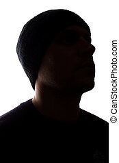 Portrait young man, unshaven, side view in cap - dark silhouette