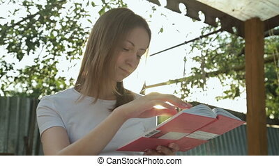 Portrait young pretty woman reading a book. Woman sitting on a bench