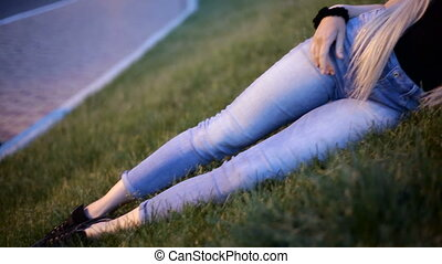 Portrait Young sexy blonde woman with very long hair resting on lawn lawn. Slide