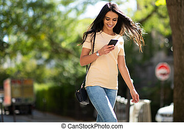 young smiling woman looking at mobile phone outside