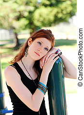 Portrait young teen girl outdoors leaning on pole