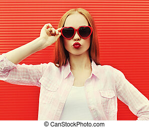 Portrait young woman blowing red lips sending sweet air kiss in heart shaped sunglasses on red wall background
