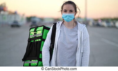 Portrait young woman courier wearing a medical mask with green bag pack