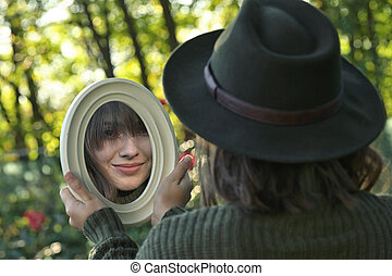 Young Woman Looking in the Mirror In Forest