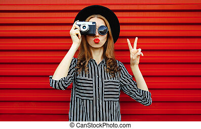 Portrait young woman photographer with vintage film camera over red wall background