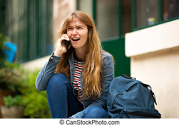 young woman sitting outside talking with mobile phone