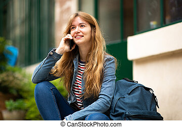 young woman sitting outside talking with phone