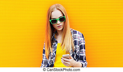 Portrait young woman with phone on city street over colorful yellow wall background