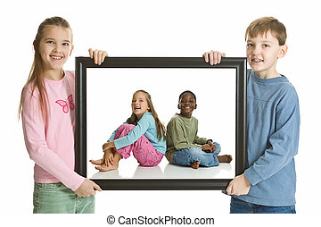 A boy and a girl holding a portrait of two younger children. Isolated on a white background.