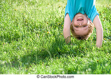 Portraits of happy kids playing upside down outdoors in summer park.