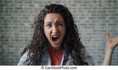 Portraot of emotional young woman screaming shaking hands on...