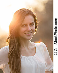 At sunset beautiful woman smiles
