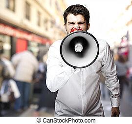 portret, od, młody mężczyzna, wrzaskliwy, z, megafon, na, miasto
