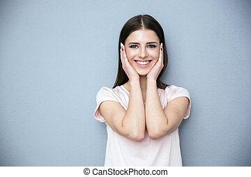portret, od, niejaki, uśmiechanie się, młoda kobieta, na, szare tło
