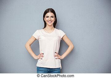 portret, od, niejaki, uśmiechanie się, młoda kobieta, stanie na drugą, szare tło